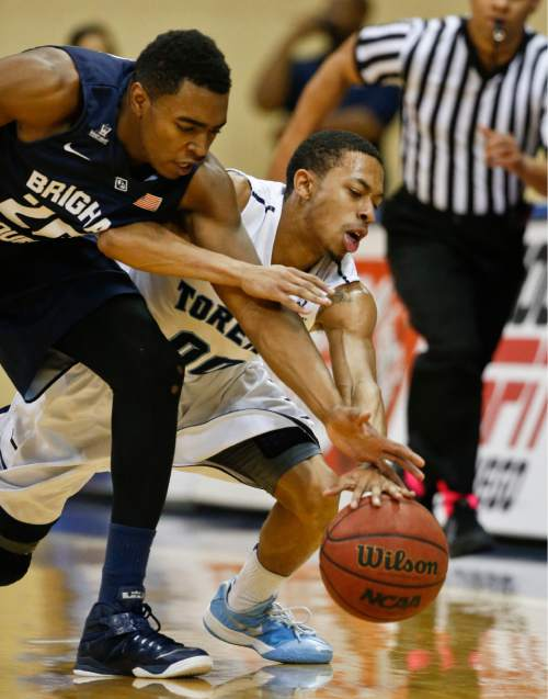 San Diego guard Christopher Anderson, right, battles BYU guard Jordan Chatman for the ball during the first half of an NCAA college basketball game Saturday, Jan. 24, 2015, in San Diego. (AP Photo/Lenny Ignelzi)