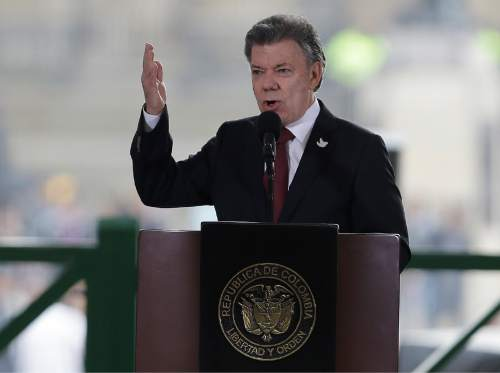 In this photo taken Nov. 6, 2015, Colombia's President Juan Manuel Santos speaks at the rebuilt Palace of Justice in Bogota, Colombia.  The White House says President Barack Obama will meet with the President Santos in February to show support for a potential peace agreement in that country. The meeting on Feb. 4 would come about seven weeks before a deadline in peace talks between Colombia's government and the Revolutionary Armed Forces of Colombia, or FARC.  (AP Photo/Fernando Vergara)