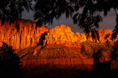 Trent Nelson  |   Tribune file photo The sun sets on peaks overlooking Springdale in October 2013. The National Park Service handled a record number of visitors last year and expects to break records again in 2016, its centennial year.