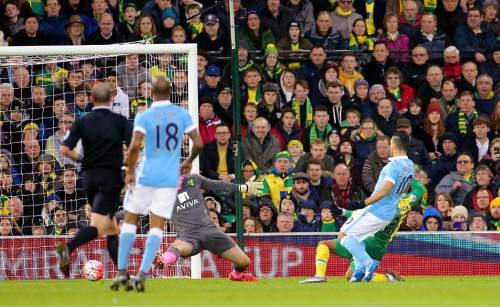 Manchester City's Sergio Aguero, right, scores his side's first goal of the match during their English FA Cup, third round soccer match against Norwich City at Carrow Road, Norwich, England, Saturday, Jan. 9, 2016. (Chris Radburn/PA via AP)      UNITED KINGDOM OUT      -     NO SALES       -       NO ARCHIVES