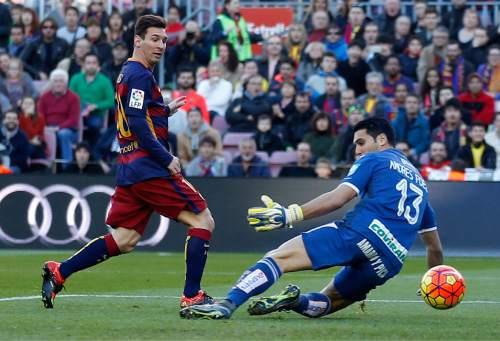FC Barcelona's Lionel Messi, left, scores past Granada's goalkeeper Andres Fernandez during a Spanish La Liga soccer match between Barcelona and Grenada, at the Camp Nou stadium in Barcelona, Spain, Saturday, Jan. 9, 2016. (AP Photo/Manu Fernandez)
