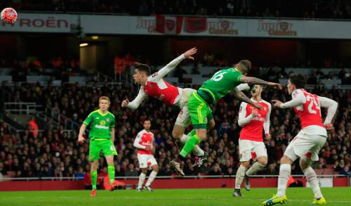 Arsenal's Gabriel, center left, jumps as he attempts to block a header by Sunderland's Steven Fletcher during the English FA Cup third round soccer match between Arsenal and Sunderland at the Emirates stadium in London, Saturday, Jan. 9, 2016 . (AP Photo/Alastair Grant)
