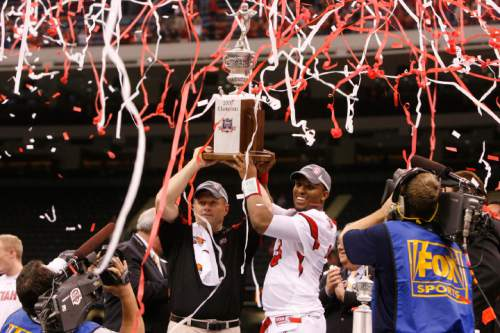 Utah head coach Kyle Whittingham  and Utah quarterback Brian Johnson (3) hold their trophy aloft after the Utes defeated Alabama in the 75th annual Sugar Bowl in New Orleans, Friday, January 2, 2009.  Scott Sommerdorf/The Salt Lake Tribune