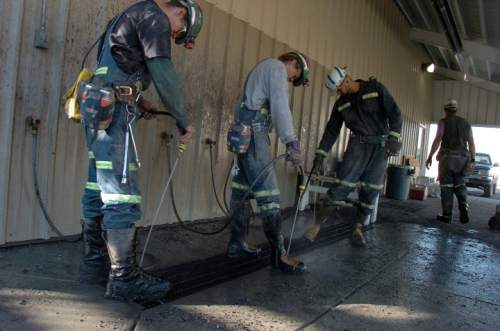 FILE - In this Aug. 28, 2009, file photo, coal miners wash their boots after leaving the Bull Mountain coal mine near Roundup, Mont. A central Montana coal mine reached an agreement Monday, Jan. 11, 2016, with environmentalists and state regulators that is intended to avoid a major shutdown as a declining coal market leaves the future of some mining companies in doubt. The deal comes after a state review panel rejected an expansion permit granted to the Bull Mountain Mine in 2013, threatening to halt most operations if the dispute could not be resolved. (AP Photo/Matthew Brown, File)