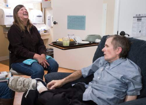 Steve Griffin  |  The Salt Lake Tribune  Carol Lynch Williams throws her head back in laughter as she visits with  longtime friend and fellow Utah author Rick Walton, who has published more than 90 picture books, as she visits him at Orchard Park Rehab in Orem in October 2015. Walton has been diagnosed with a terminal brain tumor and lives in the care facility, where author friends ó famous and not ó visit nearly daily, some bringing their latest manuscripts, seeking his feedback.  I