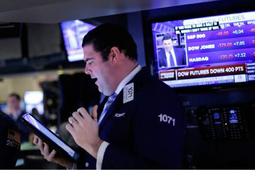 Stock trader Robert McQuade works at the New York Stock Exchange, Friday, Jan. 15, 2016. (AP Photo/Mark Lennihan)