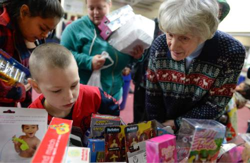 Francisco Kjolseth | The Salt Lake Tribune Homeless advocate Pamela Atkinson joins Guy Panek, 6, in picking out a Christmas present during the annual Christmas dinner to more than 800 homeless Utahns Friday at St. Vincent de Paul Dining Hall in downtown Salt Lake City.