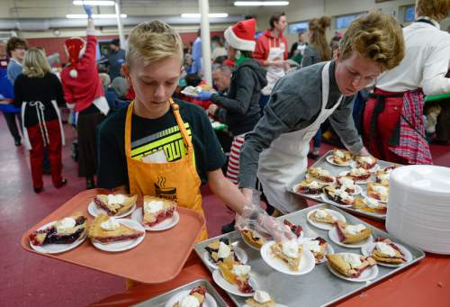 Francisco Kjolseth | The Salt Lake Tribune Soren Mickelson, 12, left, and Cody Wright, 18, fill up trays with dessert as volunteers and other community leaders serve the annual Christmas dinner to more than 800 homeless Utahns Friday at St. Vincent de Paul Dining Hall in downtown Salt Lake City.