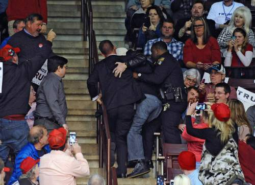 A protester is removed by two officials as Republican presidential candidate Donald Trump speaks during a campaign stop at Winthrop University on Friday, Jan. 8, 2016, in Rock Hill, S.C. (AP Photo/Rainier Ehrhardt)