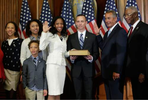 House Speaker John Boehner of Ohio administers the House oath to Rep. Mia Love, R-Utah, during a ceremonial re-enactment swearing-in ceremony, Tuesday, Jan. 6, 2015, in the Rayburn Room on Capitol Hill in Washington. Joining them are Love's husband Jason Love, center, and other family members. (AP Photo/Pablo Martinez Monsivais )