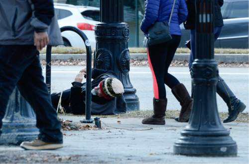 Francisco Kjolseth   The Salt Lake Tribune A man lies on the ground at Pioneer park in Salt Lake City on Tuesday. A recent poll story on homelessness tries to answer the questions surrounding funding and responsibility.