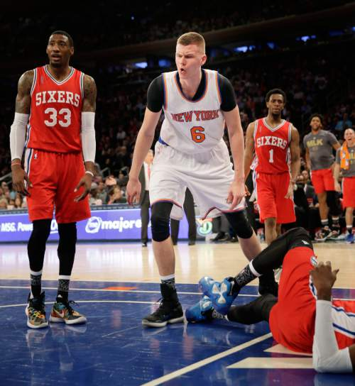 New York Knicks' Kristaps Porzingis, center, reacts after trying for a rebound during the second half of the NBA basketball game against the Philadelphia 76ers, Monday, Jan. 18, 2016 in New York. Porzingas injured his foot on the play. The Knicks defeated the 76ers in double overtime 119-113. (AP Photo/Seth Wenig)