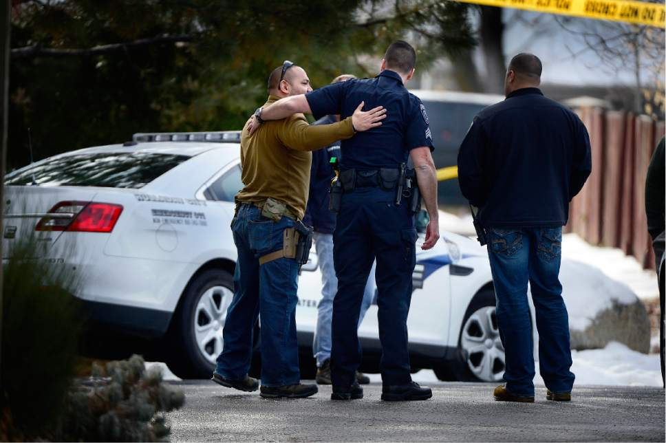 Scott Sommerdorf   |  The Salt Lake Tribune Police at the scene of an officer-involved shooting, in Holladay, Sunday, January 17, 2016. As new officers arrived at the scene, they would often hug other officers who were working the scene of the shooting.
