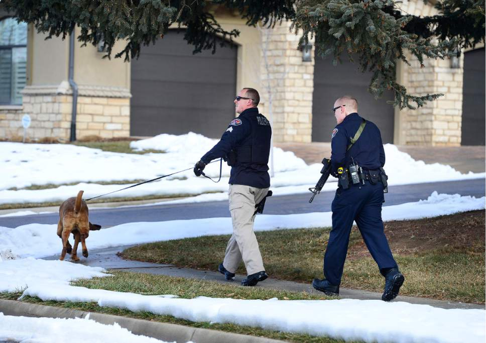 Scott Sommerdorf   |  The Salt Lake Tribune A Unified Police officer works a search of the neighborhood with a search dog and another officer. Police at the scene of an officer-involved shooting, in Holladay, Sunday, January 17, 2016.