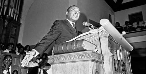 Dr. Martin Luther King Jr., tells a mass meeting in Birmingham, Alabama  Sept. 17, 1963 that Ïwords and actionsÓ of Alabama Gov. George Wallace were to blame for the deaths of four African American girls in a church bombing. The meeting of about 1,200 persons voted to state a march on the state capitol in Montgomery to protest racial violence. (AP Photo)