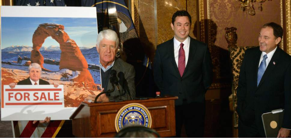 "Al Hartmann  |  The Salt Lake Tribune Utah Congressman Rob Bishop shows a poster criticising his views of federal land use as Congressman Jason Chaffetz and Governor Gary Herbert chuckle.  Bishop said that it was an old photo of him 60 lbs. heavier and that a new photo should be used. The three then unveield a ""discussion draft"" of their Public Lands Initiative bill affecting 18 million acres in seven eastern Utah counties at the  Capitol Tuesday Jan 20.  Bishop intends on introducing the bill in congress in the next few weeks."