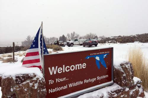 A sign of the National Wildlife Refuge System is seen at an entry of the wildlife refuge, where some vehicles are seen used to block access to the inside of the refuge, about 30 miles southeast of Burns, Ore., Sunday, Jan. 3, 2016. Armed protesters are occupying a building at the national wildlife refuge and asking militia members around the country to join them. The protesters went to Malheur National Wildlife Refuge on Saturday following a peaceful rally in support of two Oregon ranchers facing additional prison time for arson. (Les Zaitz/The Oregonian via AP)