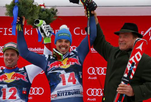 Italy's Peter Fill, center, is flanked by second placed Switzerland's Beat Feuz, left, and actor Arnold Schwarzenegger as he celebrates on the podium  after winning an alpine ski, men's World Cup downhill, in Kitzbuehel, Austria, Saturday, Jan. 23, 2016. (AP Photo/Giovanni Auletta)