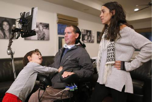 """In this Monday, Jan. 18, 2016, photo, former New Orleans Saints NFL football player Steve Gleason and his wife, Michel, pause as their 4-year-old son, Rivers, climbs onto his father's lap during an interview in their home in New Orleans. """"GLEASON,"""" a feature-length documentary that gives an unfiltered look at his life with ALS premieres at the Sundance Film Festival on Saturday. (AP Photo/Jonathan Bachman)"""