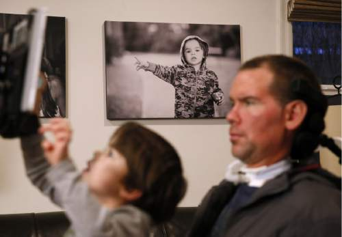 """In this Monday, Jan. 18, 2016,  photo, former New Orleans Saints NFL football player Steve Gleason watches as his four-year-old son, Rivers, plays on his father's tablet during an interview in their home in New Orleans. """"GLEASON,"""" a feature-length documentary that gives an unfiltered look at his life with ALS premieres at the Sundance Film Festival on Saturday. (AP Photo/Jonathan Bachman)"""