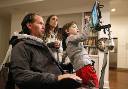 """In this Monday, Jan. 18, 2016, photo, former New Orleans Saints NFL football player Steve Gleason watches as his four-year-old son, Rivers, plays on his father's tablet as his wife, Michel, answers a question during an interview in their home in New Orleans. """"GLEASON,"""" a feature-length documentary that gives an unfiltered look at his life with ALS premieres at the Sundance Film Festival on Saturday. (AP Photo/Jonathan Bachman)"""