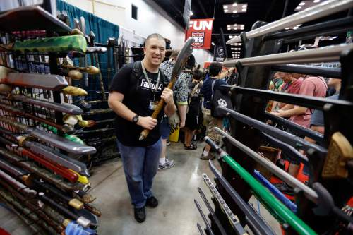 In this July 30, 2015 photo, Daniel Lavely, of Vincennes, Ind., checks out a display of replica weapons in the exhibition hall of the Gen Con gaming convention in Indianapolis. Tourism officials say Indiana may have lost as much as $60 million in revenue after a dozen conventions picked cities other than Indianapolis amid the uproar over the state's controversial religious objections law. The state Senate is scheduled to take up measures addressing LGBT rights on Wednesday. (AP Photo/Michael Conroy)