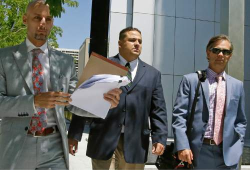 Rick Bowmer  |  AP file photo Jon Martinson Jr., center, an Immigration and Customs Enforcement agent accused of slamming a man's face into a concrete floor, walks with his attorneys in 2015 following a hearing at the federal courthouse in Salt Lake City. Martinson has pleaded not guilty to violating federal laws and constitutional rights in the June 2013 incident.