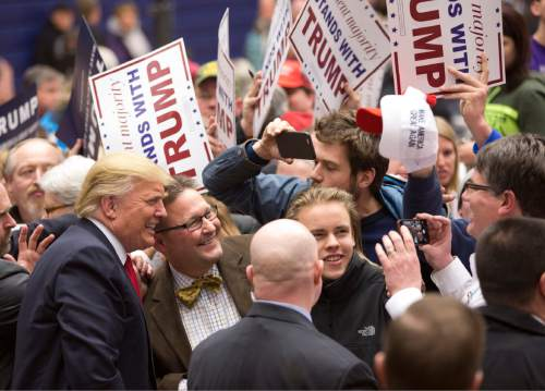 Republican presidential candidate Donald Trump, left, poses for a photograph with a supporter during a campaign event at the Roundhouse Gymnasium, Tuesday, Jan. 26, 2016, in Marshalltown, Iowa. (AP Photo/Mary Altaffer)