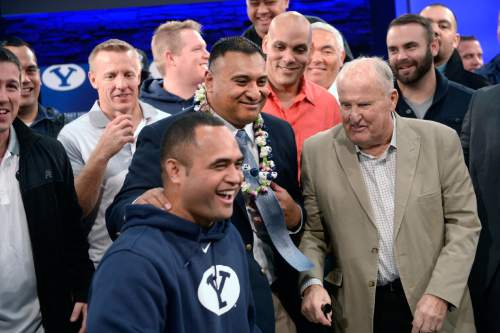 Al Hartmann  |  The Salt Lake Tribune BYU football players and staff gather around new head coach Kalani Sitake, center, and his old coach Lavell Edwards, right, after a press conference in Provo Monday Dec. 21.