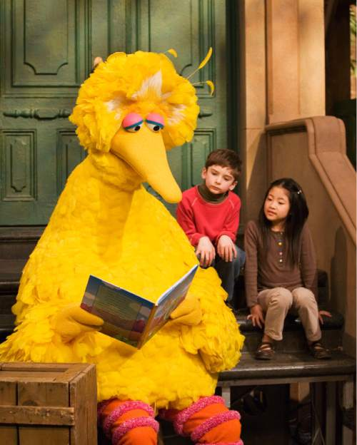 "FILE - In this April 10, 2008 file photo, muppet character Big Bird reads to Connor Scott and Tiffany Jiao during a taping of  the children's program ""Sesame Street"" in New York. Sesame Street continues to attract millions of viewers after 45 years on the air, appealing to both preschoolers and their parents with content that is educational and entertaining. The show has kept up with the times by making its segments faster-paced, by fine-tuning messages, and by keeping a steady flow of appearances by contemporary celebrity guests. The show first aired Nov. 10, 1969. (AP Photo/Mark Lennihan, File)"