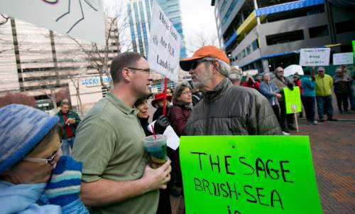 """Keep Public Lands Public"" rally attendee Richard Prange (right) argues with and unidentified attendee (left, he refused to give his name) of a Western Rangelands Property Rights Workshop held at the Boise Centre in Boise, Idaho. Saturday January 30, 2016. Kyle Green for The Salt Lake Tribune"