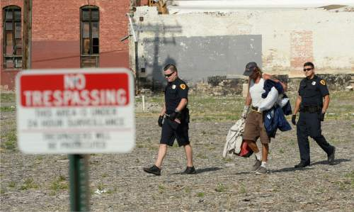 Al Hartmann  |  The Salt Lake Tribune Salt Lake Police escort a homeless man with his camping gear across a lot posted no tresspassing at 500 W. and 350 S.  It's an area where homeless are camping out on the 500 West Commons just west of the Rio Grande Depot.