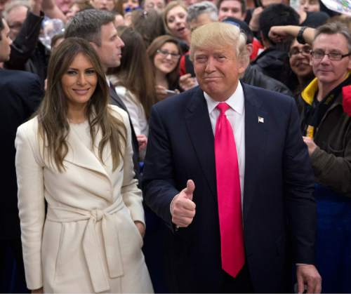 Republican presidential candidate Donald Trump gives a thumbs up as he and wife, Melania, pause for photos at a rally Sunday, Jan. 31, 2016, in Council Bluffs, Iowa. (AP Photo/Jae C. Hong)