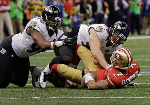 Baltimore Ravens linebacker Paul Kruger (99)  sacks San Francisco 49ers quarterback Colin Kaepernick (7) as defensive end Pernell McPhee (90) helps in the first quarter of the NFL Super Bowl XLVII football game Sunday, Feb. 3, 2013, in New Orleans. (AP Photo/Dave Martin)