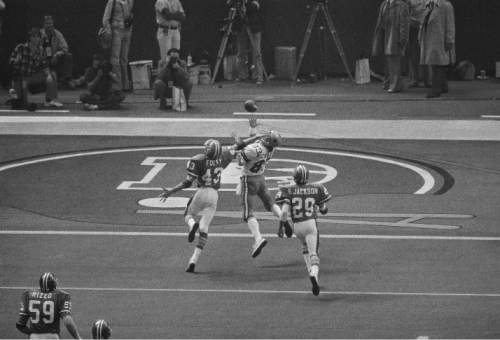 Despite the effort of Denver defensive back Steve Foley (43), wide receiver Golden Richards of Dallas hauls down a touchdown pass from Robert Newhouse in Super Bowl XII in New Orleans, La., Jan. 15, 1978. (AP Photo)