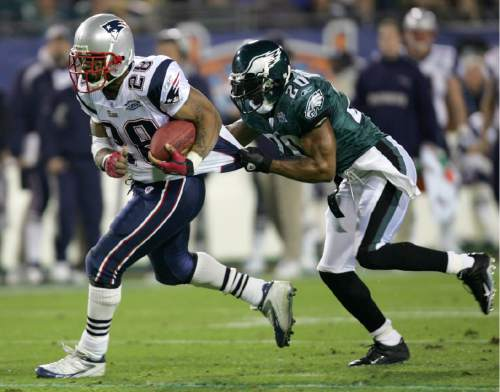 New England Patriots running back Corey Dillon (28) picks up yardage before being tackled by Philadelphia Eagles free safety Brian Dawkins (20) in the second quarter of Super Bowl XXXIX at Alltel Stadium on Sunday, Feb. 6, 2005, in Jacksonville, Fla. (AP Photo/David J. Phillip)