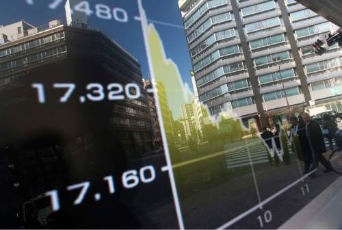 Pedestrians are reflected on an electronic stock board showing Japan's Nikkei 225 chart at a securities firm in Tokyo, Wednesday, Feb. 3, 2016. Asian shares stumbled Wednesday as another steep drop in the price of oil reinforced worries about the potential impact on the world economy of job cuts and reduced investment in the energy industry. (AP Photo/Eugene Hoshiko)