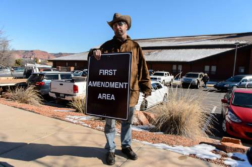 "Trent Nelson  |  The Salt Lake Tribune Greg Whalen holds a ""First Amendment Area"" sign he says came from the Bundy ranch in Nevada, at the funeral for Robert ""LaVoy"" Finicum, in Kanab, Friday February 5, 2016. Finicum was shot and killed by police during a January 26 traffic stop. Finicum was part of the armed occupation of an Oregon wildlife refuge."