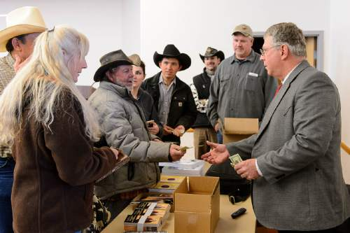 Trent Nelson  |  The Salt Lake Tribune Angus McIntosh sells study materials to some of the eighty people (ranchers and media) who attended a public lands workshop at the public library in Kanab, Saturday February 6, 2016. Kanosh attorney Todd Macfarlane said he also hoped to help outsiders better understand the importance of land use to area ranchers.