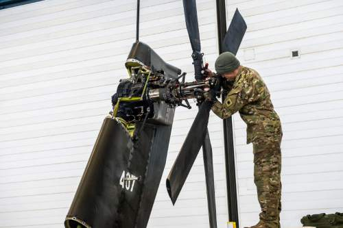 """Chris Detrick     The Salt Lake Tribune Technician Sgt. Andrew Riggs works on the tail rotor and swashplate on a AH-64 Apache helicopter at the Utah National Guard aviation armory in West Jordan Thursday February 4, 2016. """"I love turning wrenches on these birds,"""" said Riggs."""