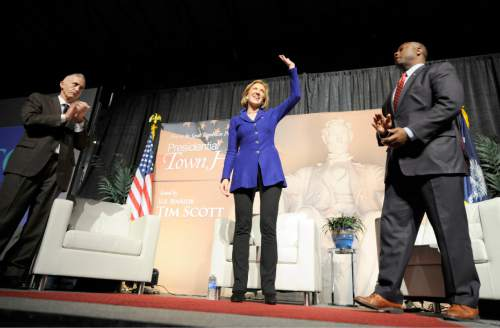 Flanked by U.S. Rep. Trey Gowdy, R-S.C, left, and U.S. Sen. Tim Scott, R-S.C, right, Republican presidential candidate Carly Fiorina acknowledges applause from the crowd at the conclusion of a town hall meeting at the University of South Carolina at Aiken Convocation Center, Friday afternoon, Oct. 2, 2015, in Aiken, S.C.  (Michael Holahan/The Aiken Standard via AP) MANDATORY CREDIT