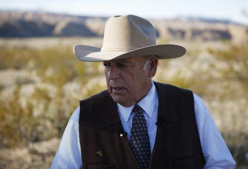 In this Jan. 27, 2016, file photo, rancher Cliven Bundy stands along the road near his ranch Wednesday, Jan. 27, 2016, in Bunkerville, Nev. Bundy, the father of the jailed leader of the Oregon refuge occupation and who was the center of a standoff with federal officials in Nevada in 2014, was arrested in Portland Wednesday night. (AP Photo/John Locher)