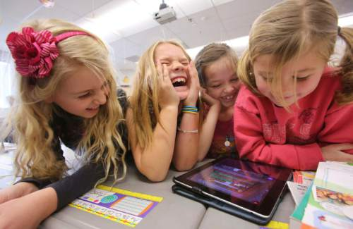 Francisco Kjolseth  |  The Salt Lake Tribune Freedom Elementary 2nd graders, Avery Sherratt, Kate Durfey, Hannah Dajany and Lilly Adams, from left, crack up when the movements of their robot don't go as planned while using code instruction on an iPad on Tuesday, Dec. 10, 2013 in Highland, Utah.
