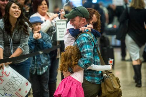Chris Detrick  |  The Salt Lake Tribune Sergeant first class Mack Christensen hugs his daughters Heidi, 5, and Tamsine, 7, at the Salt Lake International Airport on Friday February. Soldiers assigned to the Utah Army National Guard's 19th Special Forces Group returned to Utah on Friday after a six-month deployment in Afghanistan.