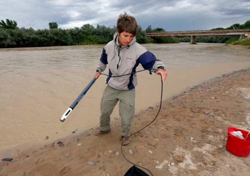 Ben Brown, with the Utah Department of Environmental Quality, takes a pH level reading from a probe in the San Juan River, Tuesday, Aug. 11, 2015, in Montezuma Creek, Utah. A spill containing lead and arsenic from the abandoned Gold King Mine in Silverton, Colo., leaked into the Animas River, which flows into the San Juan River in southern Utah, on Aug. 5. The spill was caused by a mining and safety team working for the EPA.  (AP Photo/Matt York)