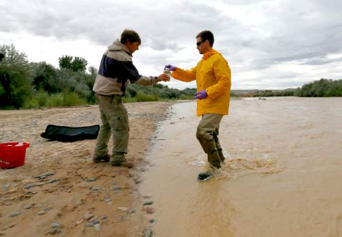Ben Brown, with the Utah Department of Environmental Quality, left, collects a water sample from the San Juan River from hydrologic technician Ryan Parker, Tuesday, Aug. 11, 2015, in Montezuma Creek, Utah.  A spill containing lead and arsenic from the abandoned Gold King Mine in Silverton, Colo., leaked into the Animas River, which flows into the San Juan River in southern Utah, on Aug. 5. The spill was caused by a mining and safety team working for the EPA.  (AP Photo/Matt York)