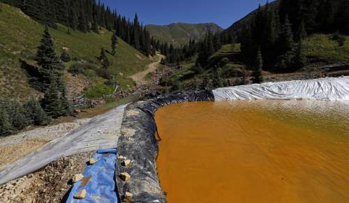 Water flows through a series of sediment retention ponds built to reduce heavy metal and chemical contaminants from the Gold King Mine wastewater accident, in the spillway about 1/4 mile downstream from the mine, outside Silverton, Colo., Friday, Aug. 14, 2015. Officials have said that federal contractors accidentally released more than 3 million gallons of wastewater laden with heavy metals last week at the Gold King Mine near Silverton. The pollution flowed downstream to New Mexico and Utah. (AP Photo/Brennan Linsley)
