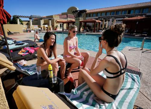 From left; Chandler Maxwell, of New Hampshire, Caitlin Johnson, of Michigan, and Devon Martin, of Saint Lucia, sit poolside, Friday, Feb. 12, 2016, at the Tempe Mission Palms hotel in Tempe, Ariz. Phoenix is expected to set a warm wether record this week with temperatures in the 80's (AP Photo/Matt York)