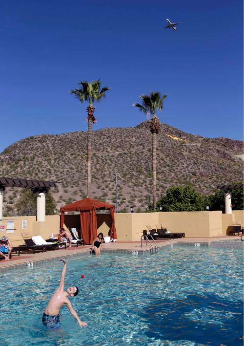 Guests enjoy the pool as a flight comes in for approach, Friday, Feb. 12, 2016, at the Tempe Mission Palms hotel in Tempe, Ariz. Phoenix is expected to set a warm wether record this week with temperatures in the 80's (AP Photo/Matt York)