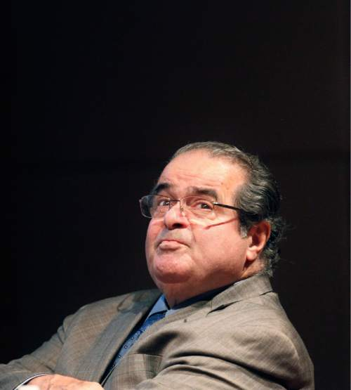 FILE - In this Oct. 18, 2011 file photo, U.S. Supreme Court justice Antonin Scalia looks into the balcony before addressing the Chicago-Kent College Law justice in Chicago. On Saturday, Feb. 13, 2016, the U.S. Marshals Service confirmed that Scalia has died at the age of 79. (AP Photo/Charles Rex Arbogast, File)